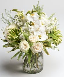 white orchids, roses and stock in a cylinder vase