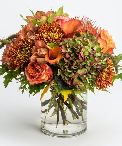 mango calla lilies and antique hydrangea in glass cylinder vase