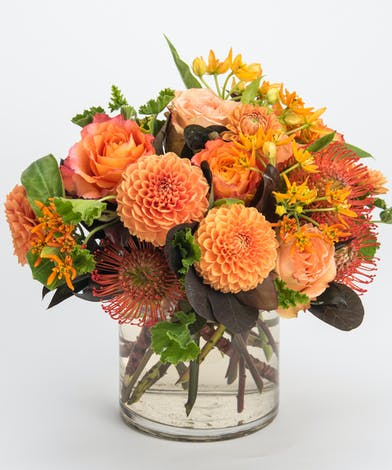 orange dahlias, peach roses, and pincushion protea autumn arrangement