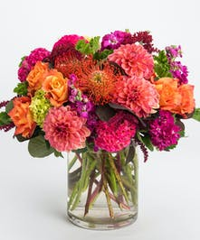 magenta stock, orange roses, and pink dahlia flower arrangement