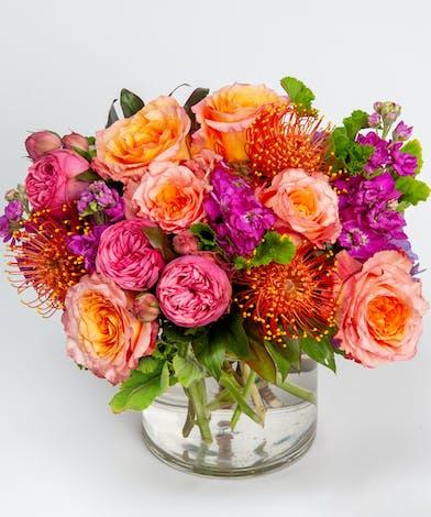 orange protea and hot pink garden roses fall flower arrangement