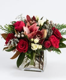 white amaryllis and red roses in a cylinder vases