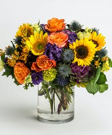 sunflowers, orange roses, and purple lisianthus in a cylinder vase