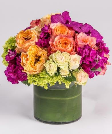hot pink orchid, orange roses, and magenta stock arrangement