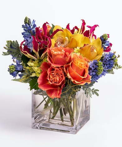 orange roses, yellow orchids and blue hyacinth flower arrangement
