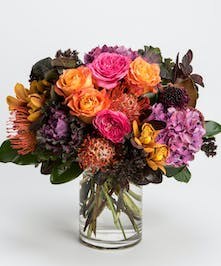 arrangement of hot pink roses, purple hydrangea and bronze cymbidiums in a clear glass vase