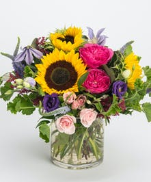 natural arrangement of sunflowers, garden roses and purple veronica