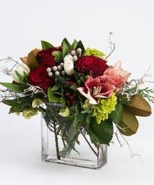 roses, amaryllis and tulips accented with seasonal greens in a glass envelope vase