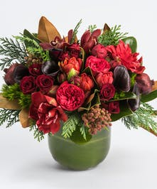 calla lilies, red roses and orchids accented with magnolia and winter berries