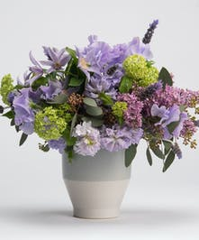 lavender sweet pea, lilac, and clematis in a ceramic container