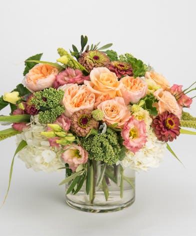 peach roses, pink lisianthus and mauve zinnias arrangement