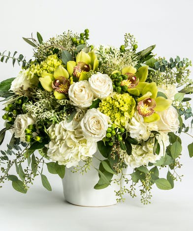 unique arrrangement of orchids, hydrangea, roses and textural greens