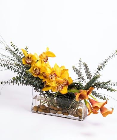 asymmetrical design of golden cymbidium orchids and mango calla lilies in a rectangular glass vase