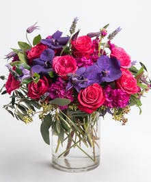 hot pink roses, fuchsia stock and purple orchids arrangement