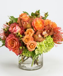 orange roses, protea, and bronze cymbidium orchids in a clear glass vase
