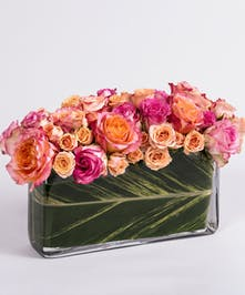 pink and peach roses in a rectangular glass vase