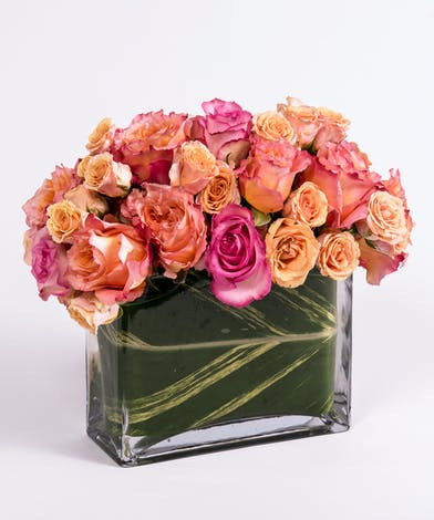 pink, peach and orange roses in a rectangular glass vase