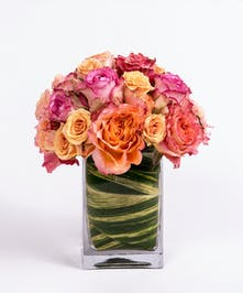 pink, orange and peach roses in a leaf-lined glass vase