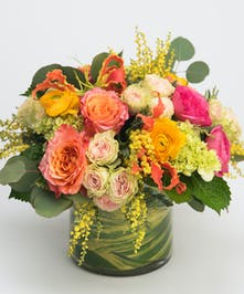 lush arrangement of citrus toned roses, ranunculus and gloriosa lilies