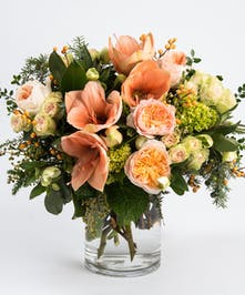 peach amaryllis and garden roses accented with gold winter berry and seasonal greens