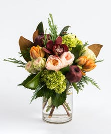orange tulips, burgundy cymbidium orchid and peach roses accented with magnolia