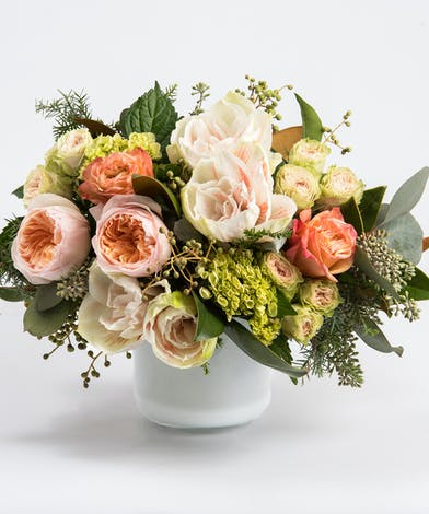 peaches roses and amarylis accented with seasonal greens