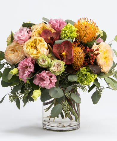 fall flower arrangement of coral orchids and peach roses