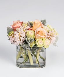 peach roses and pink hyacinth in recycled glass container