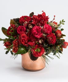 red orchid, roses and amaryllis in a copper container