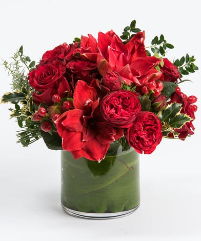 Red roses and amaryllis with red berries in cylinder vase. Philadelphia Florist