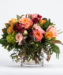 flower arrangement of orange tulips, pink roses and red spray roses with seasonal greens
