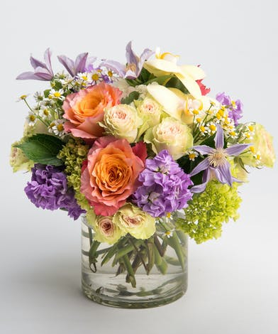 citrus toned flower arrangement with roses, orchids and clematis