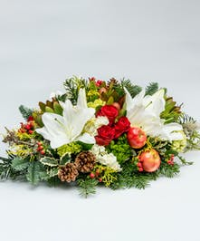 christmas centerpiece of roses, lilies and greens