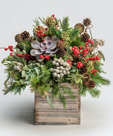seasonal greens accented with succulents and red berries in a wooden cube