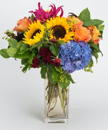 Autumn arrangement of sunflowers, orange roses and blue hydrangea
