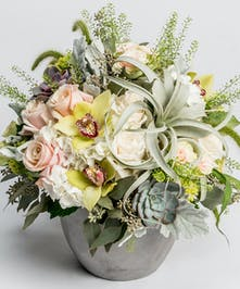 unique arrrangement of orchids, hydrangea, succulents and air plants