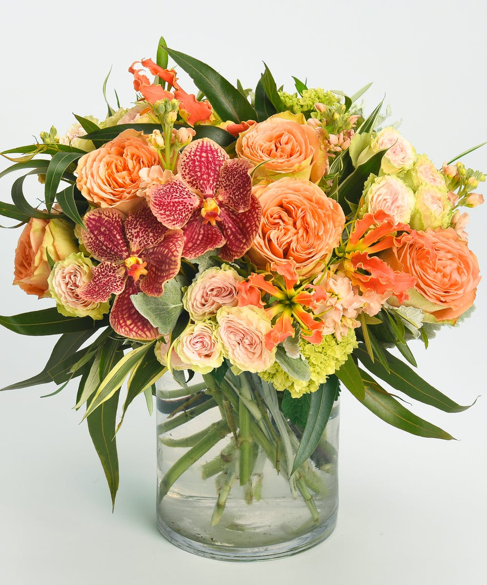 summery design of orchids, gloriosa lilies and roses