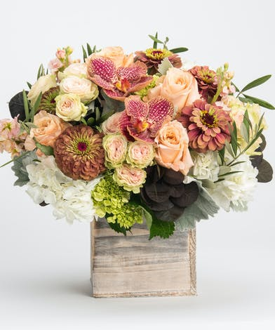 arrangement blush and peach tones desinged in wooden boxes