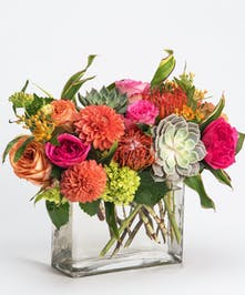 unique arrangement of dahlias, roses and succulents in rectangular glass vase