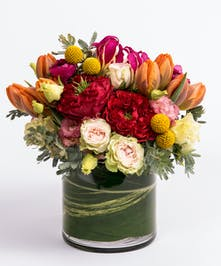 unique floral design of red roses, orange tulips, gloriosa lilies and craspedia