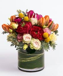 unique floral design of red roses, orange tulips, gloriosa lilies and craspedia