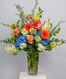 funeral flower arrangement of all vibrant blooms in a clear glass vase
