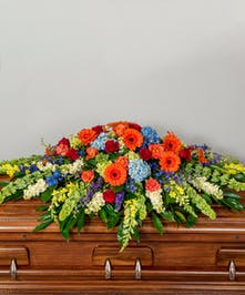 funeral cakset spray of vibrant orange, yellow and blue flowers