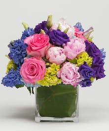 low and lush arrangement of vibrant pastel flowers