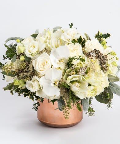 Unique floral design of white amaryllis, hydrangea and orchids in a copper container