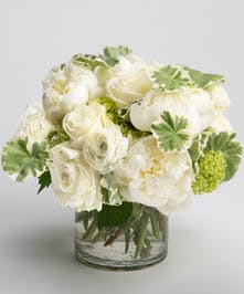 white roses, hydrangea and orchids in white glass vase
