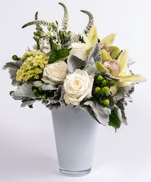 white roses and hydrangea accented with green orchids in a white glass vase