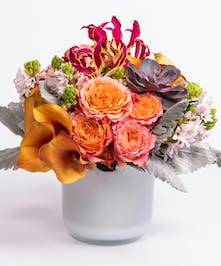 mango calla lilies, orange roses and gloriosa lilies in a white glass cylinder vase