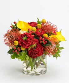 fall arrangement of yellow calla lilies and red monster roses in a glass cylinder vase