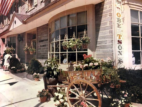 A wooden cart holds potted plants in this 1950s look at the exterior of our downtown location